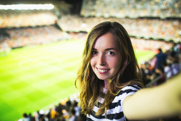 Sexy female supporter makes selfie at football game in Barcelona