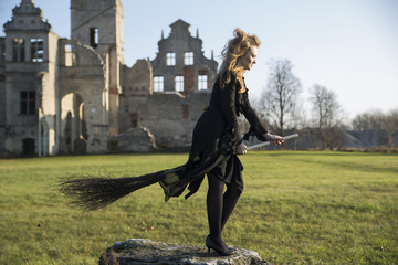 Witch with pale skin on ruins background