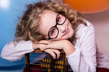 Funny, clever curly teen girl in glasses with wooden abacus on t