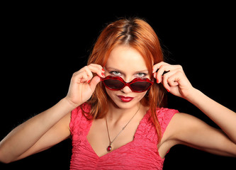 Girl with heart-shaped glasses and closed eyes smiling