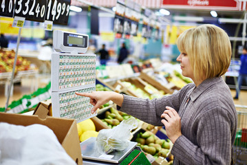 Young woman weighing pears in store