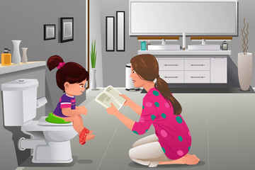 Girl doing potty training with her mother watching