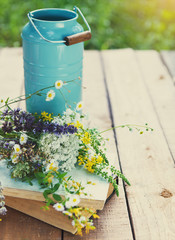 Flowers near watering can with old books on a rustic wooden tabl