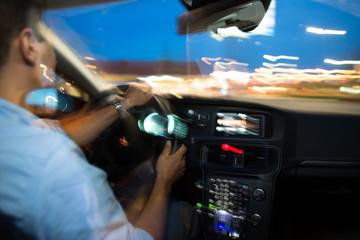 Driving a car at night - young man driving his modern car