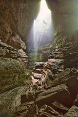 Man Rappels into cave