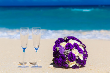 Wedding bouquet and two glasses of champagne on the sand. Blue s