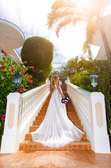 Beautiful bride in wedding dress with long train standing on the