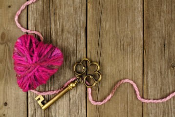 Valentines Day background with wool heart and key on old wood