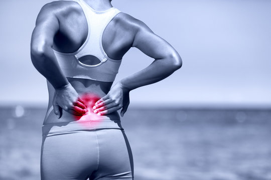 Back pain. Athletic running woman with back injury
