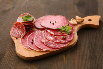 Fototapete - Various sliced salami with garlic, dill and spices