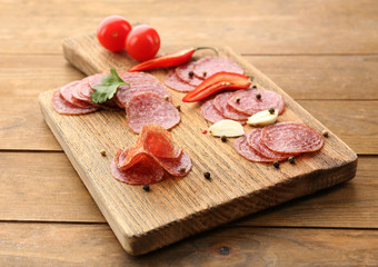 Fototapete - Slices of salami with spices and vegetables