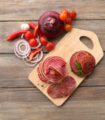 Fototapete - Sliced salami with chili pepper, cherry tomatoes, onion and