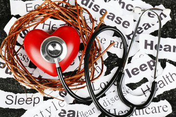 Decorative heart  with stethoscope on background of paper notes
