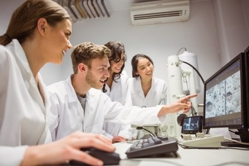 Science students looking at microscopic image on computer