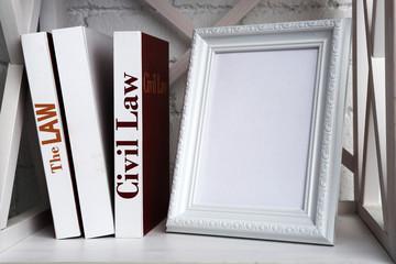 Photo frame with books on shelf, on brick wall background