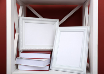 Photo frames with books on shelf, on color wall background