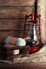 Kerosene lamp with yarn and needles for knitting in wicker