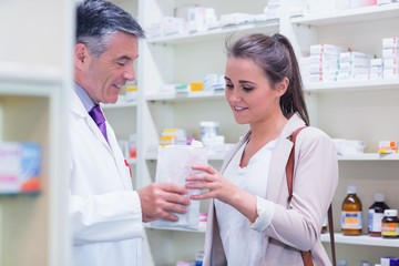Pharmacist giving paper bag to his customer