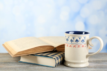 Cup of tea and books on table, on bright background