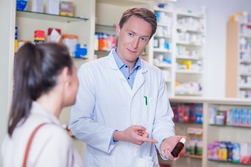 Pharmacist pointing a flask of pills in front of a customer