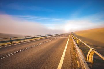 Long bridge in the fog, between fields