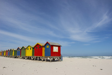 Colourful wooden buildings on Muizenberg beach with kelp