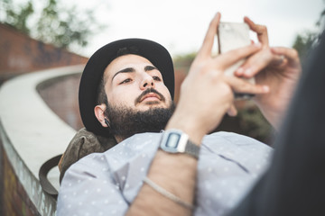 young handsome hipster gay modern man using smartphone