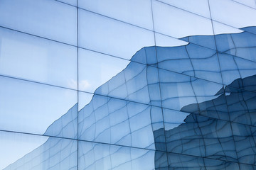 facade of modern glass building with reflections of blue sky and