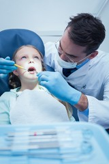 Male dentist examining girls teeth