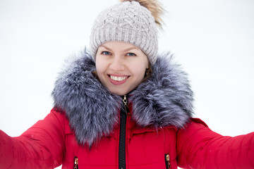 Happy young female in red winter jacket taking self-portrait, ou