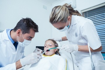 Male dentist  with assistant examining girls teeth
