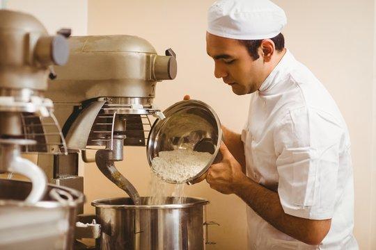 Baker pouring flour into large mixer