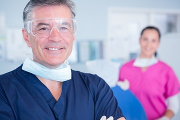 Smiling dentist with protective glasses
