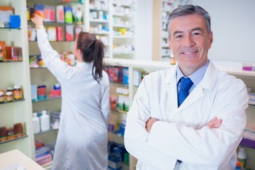 Pharmacist looking at camera with student behind him