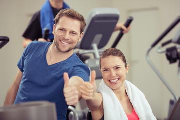 paar im fitness-studio zeigt daumen hoch