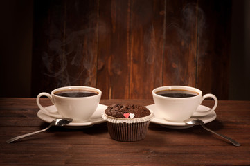 Delicious tasty cupcake and two coffe cup on wooden table