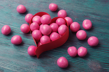 Sweet pink candies in heart shaped box on vintage wooden backgro