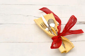 vintage silverware inside yellow napkin and red bow