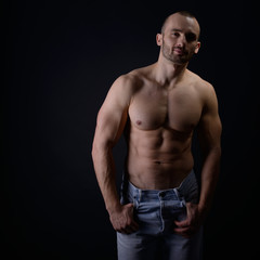 Strong athletic man with perfect body posing in studio on black