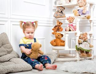 Little girl holding a teddy bear. Little girl in denim overalls