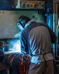 Welder working steel