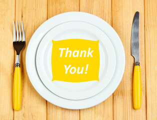 "Plate with text ""Thank you"", fork and knife on wooden"