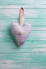 Textile heart  on aqua wooden background.