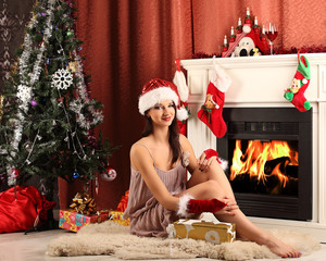 Christmas girl near the fireplace and tree