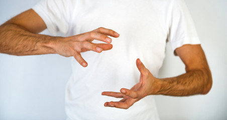 Man making a gesture to clasp a round object
