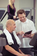 trainer erklärt einem senior im fitness-studio den trainingsplan
