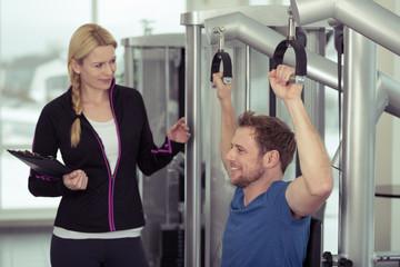 trainerin berät einen mann am fitness-gerät
