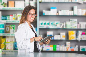 Beautiful Pharmacist with Digital Tablet in a Drugstore
