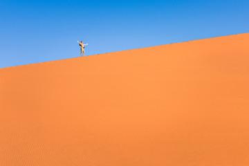 Adventurous man lonely traveler hiking on sand dune at Deadvlei