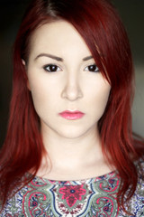 Redhead young woman in bright colorful top portrait